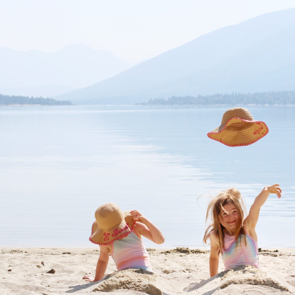 a little girl throws her hat on the beach