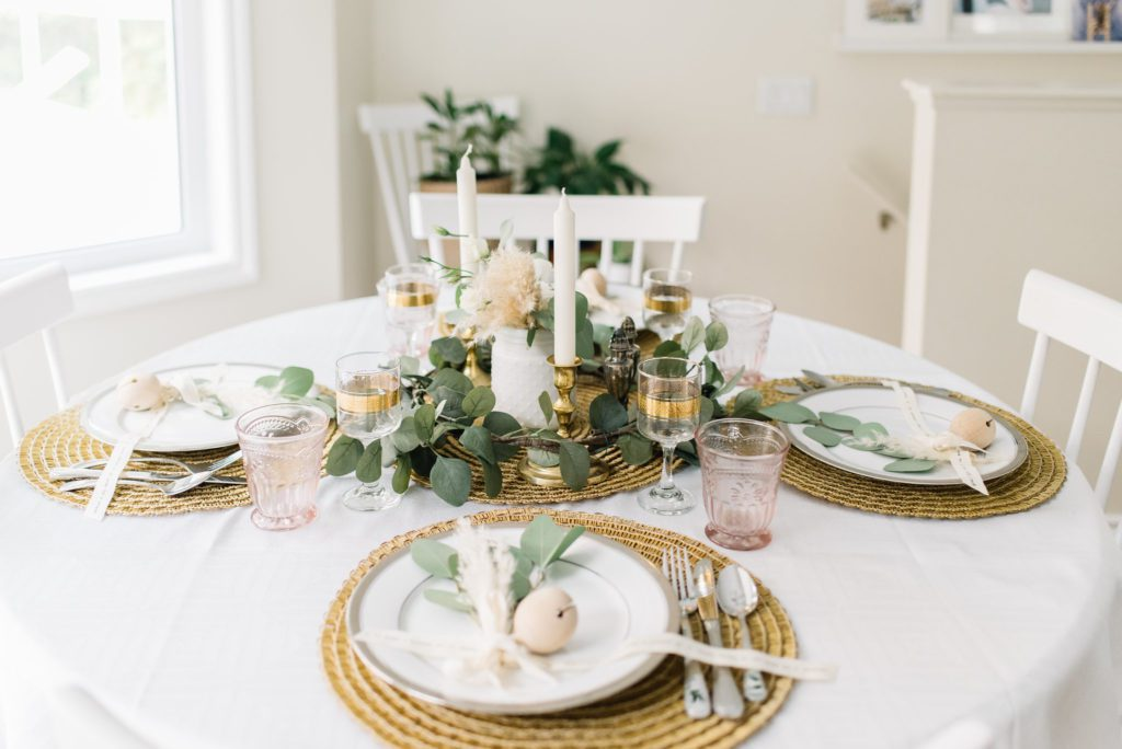 A dining table with greenery and gold accents