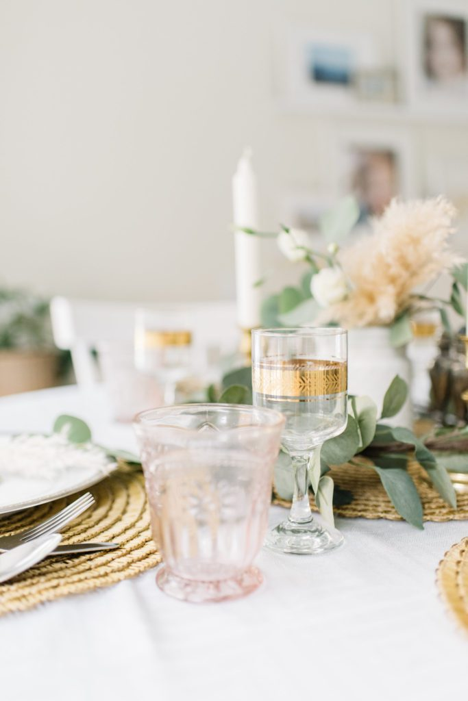 A vase of flowers on a table with gold filigree glasses