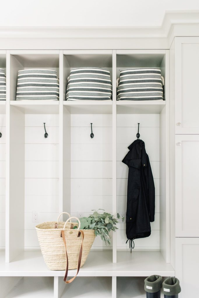 Open lockers with coat hooks and storage bins allow for quick access in this mudroom design