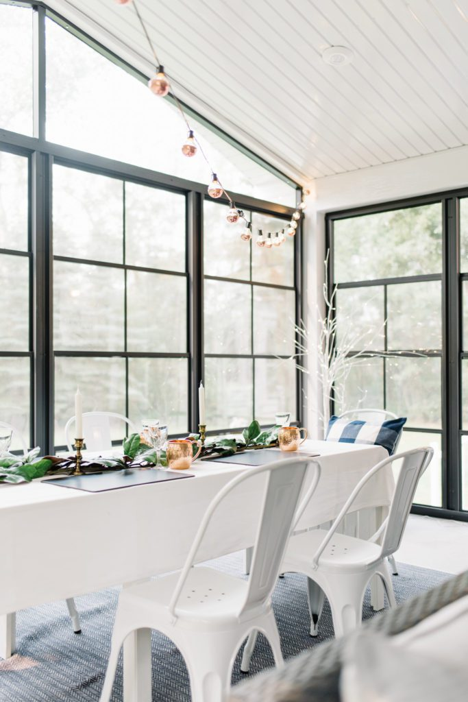 A sunroom with black floor to ceiling windows