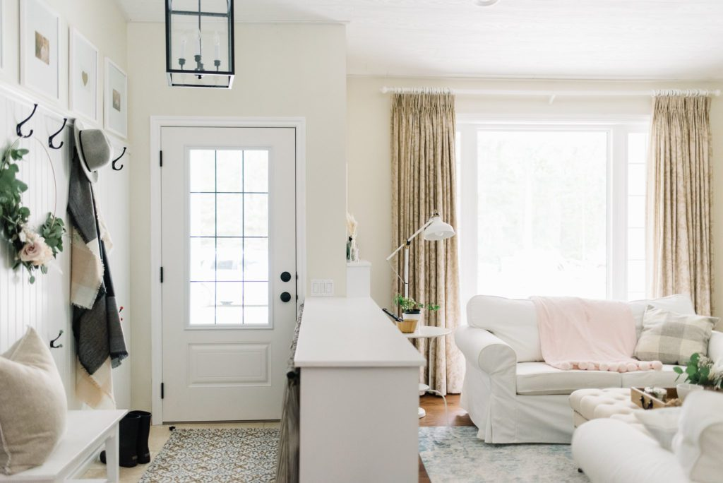small entryway delineated by a half wall separating the entryway from the living room