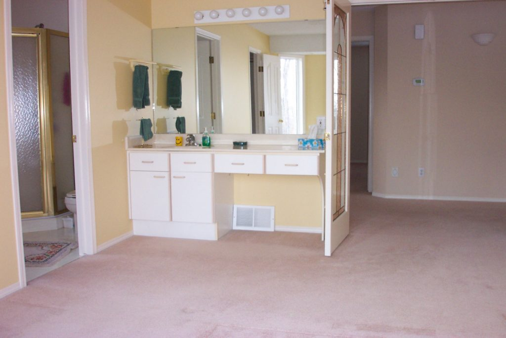 master bedroom before renovation with sink in bedroom and yellow walls