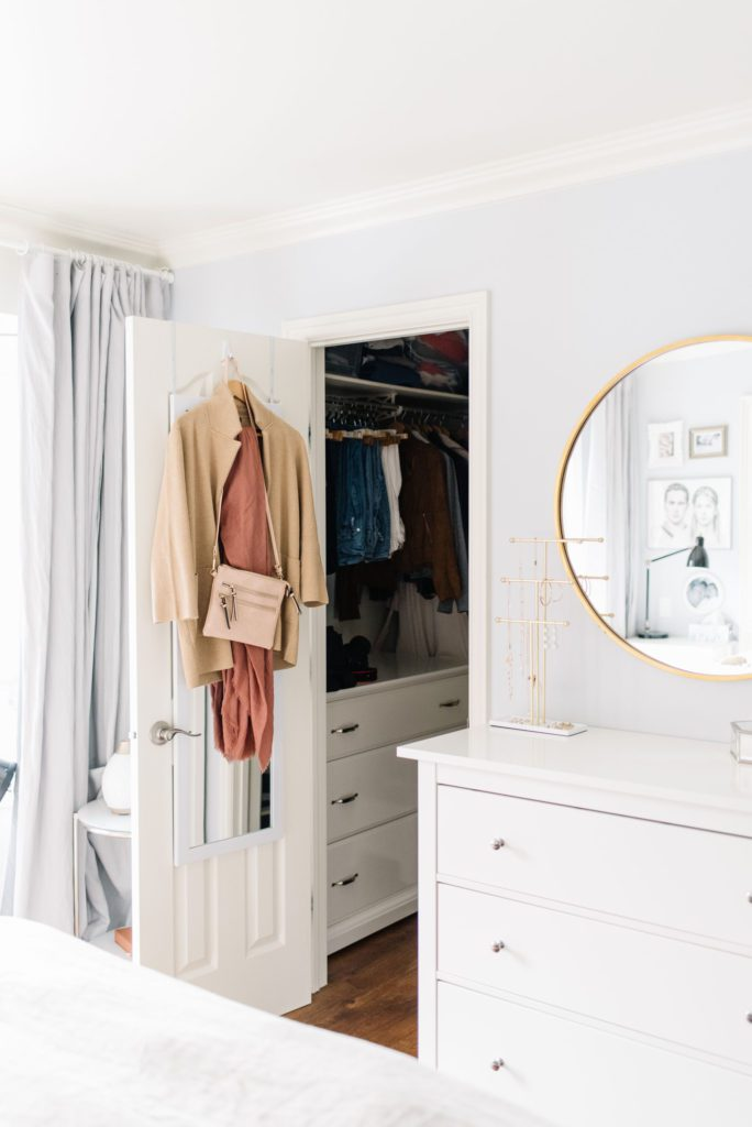 A small master bedroom closet with a dresser added for storage and clothing hanging on the door.