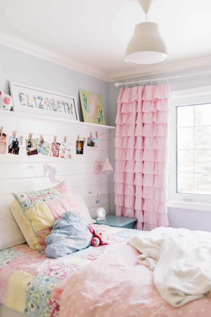 A small bedroom is cheerful with bright colours and functional shelving