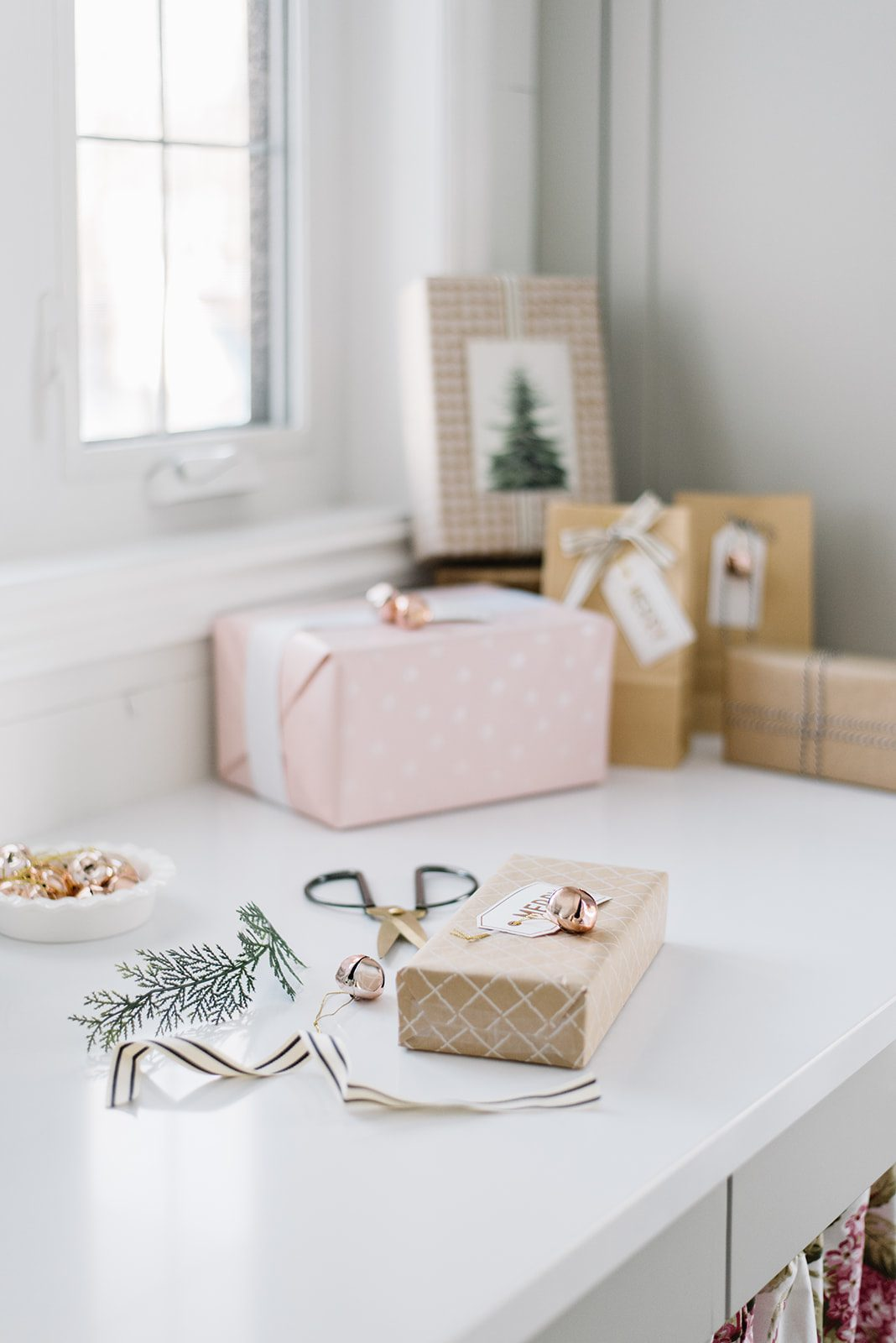 wrapped presents sit on a counter beside scissors and ribbon