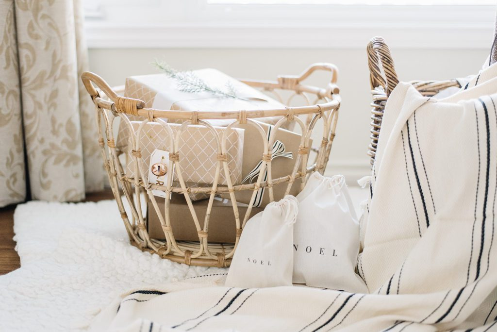 A rattan basket filled with presents wrapped in brown paper