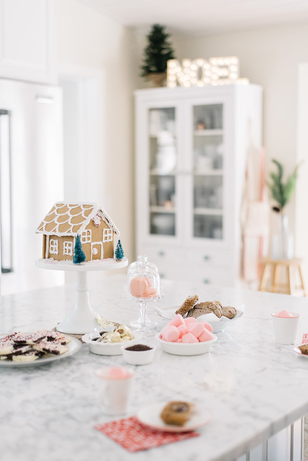 gingerbread house sits on a white cake pedestal beside cookies and marshmallows