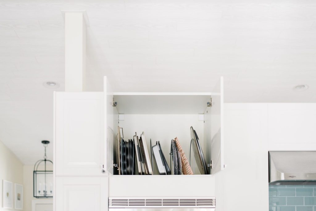 Cooling racks are stored vertically in  the cupboard above the ovens to save space in a small kitchen