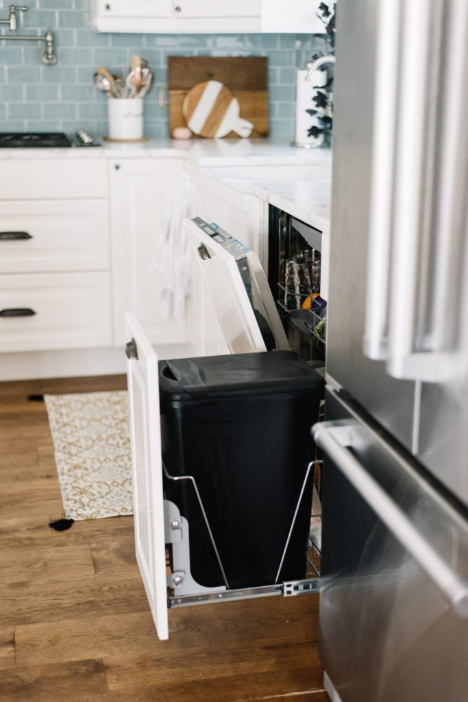 open dishwasher and garbage pullout in kitchen