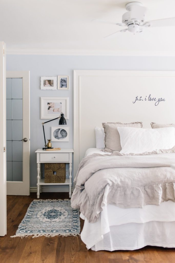 Bedside tables with drawers and baskets maximize storage in this small master bedroom