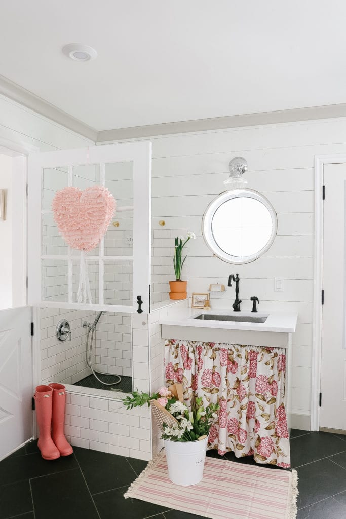 Farmhouse mudroom decorated for Valentines day with a heart pinata and pink hunter boots