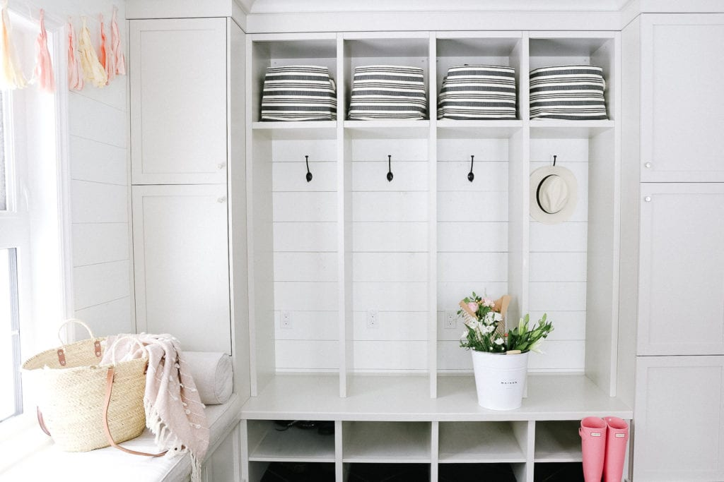 mudroom with striped baskets and a large bucket of flowers