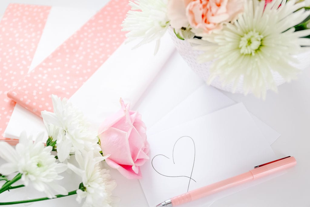handwritten note on a table with flowers