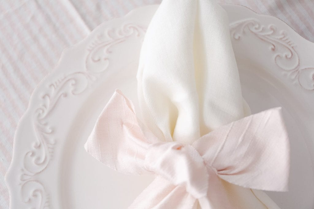 A close up of a napkin tied with pink silk ribbon