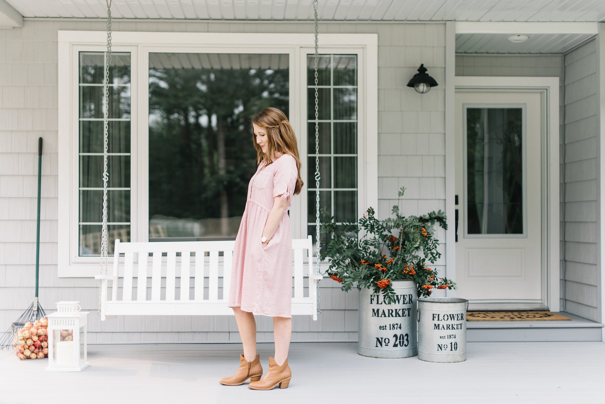 woman standing on front porch in a pink dress