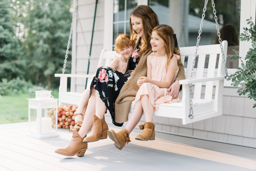 A woman sitting on a bench with little girls