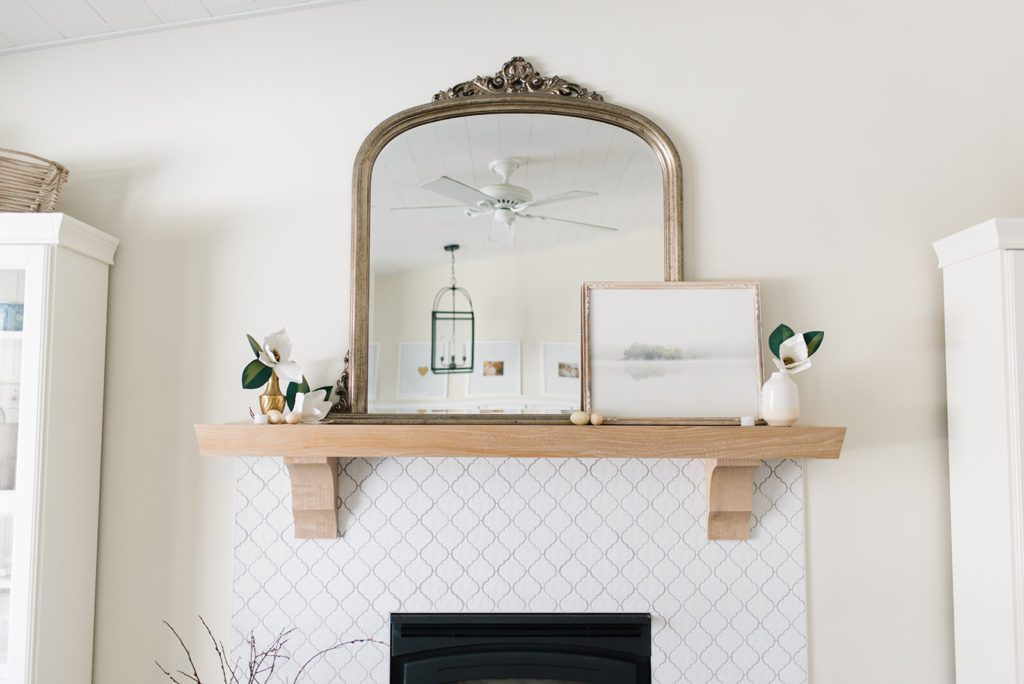 white oak fireplace mantle with a gold mirror