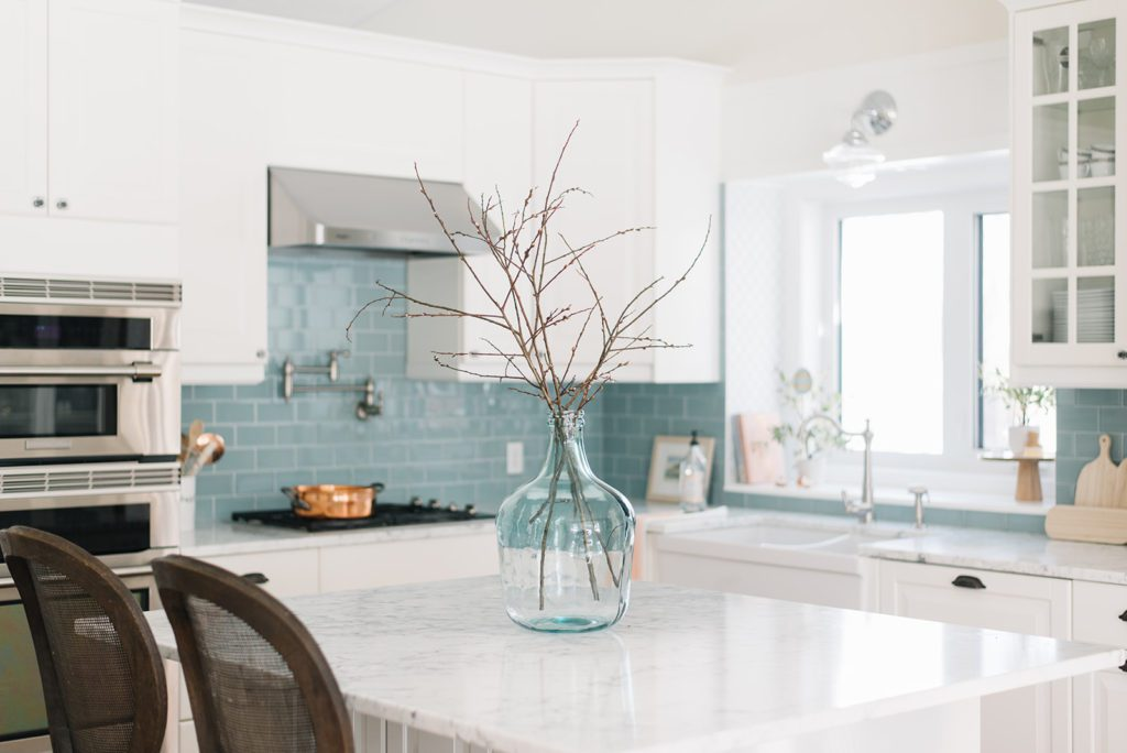 A large blue glass vase filled with branches on a kitchen island