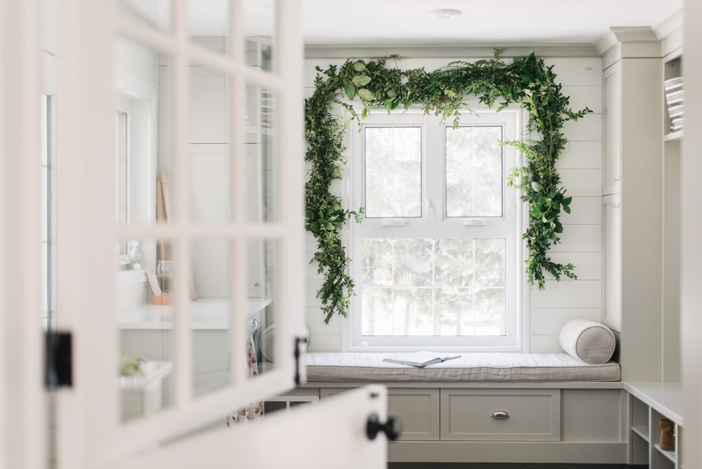 a fresh garland of greens hung above a large window