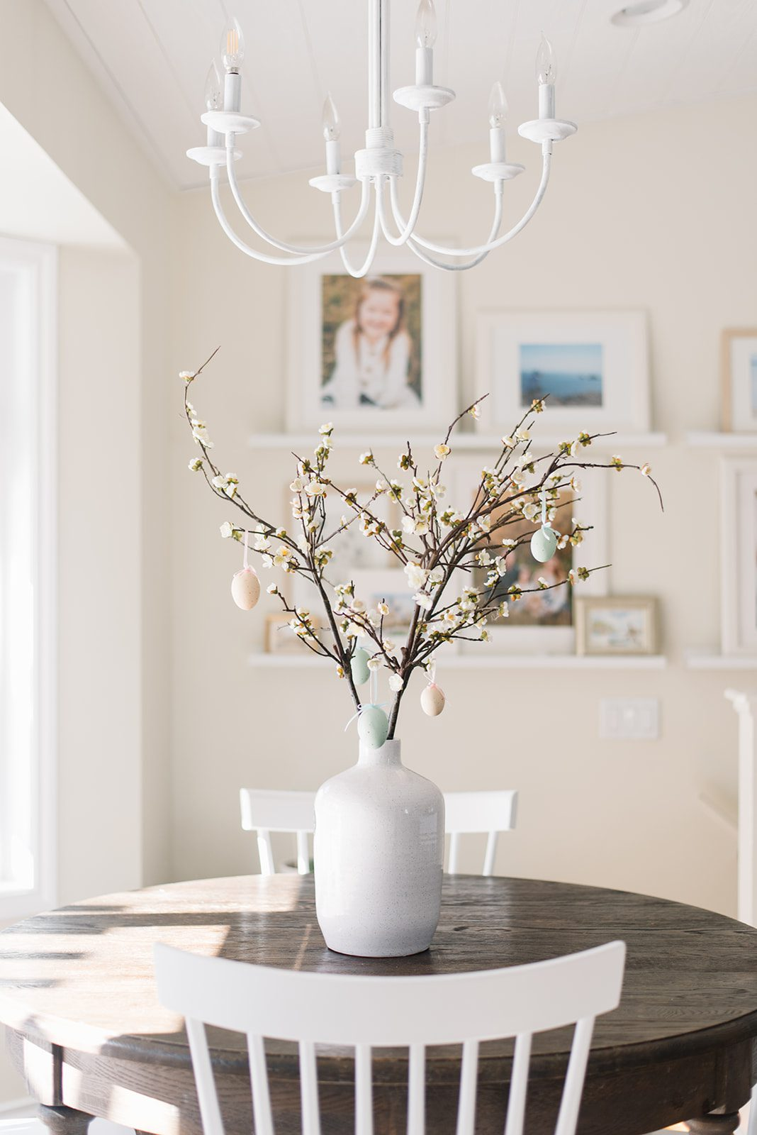 A vase of pussy willows with Easter eggs hung on the branches