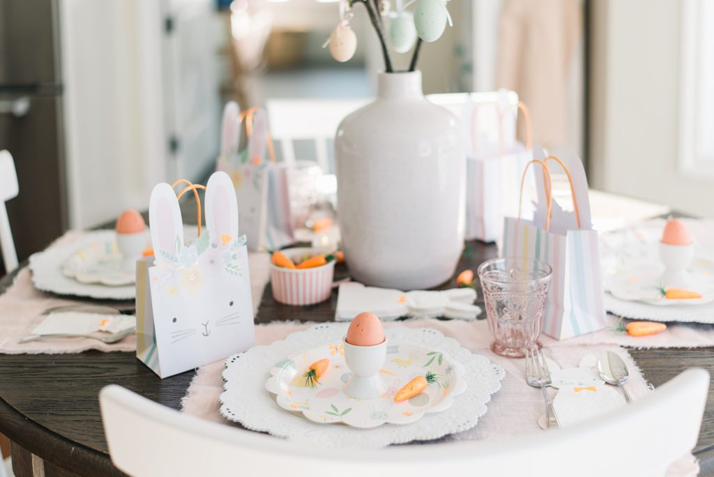 An Easter table set with pink, orange and white decorations