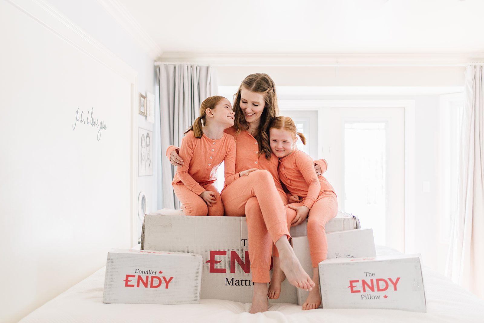 Woman and kids sit on an Endy bed in a box