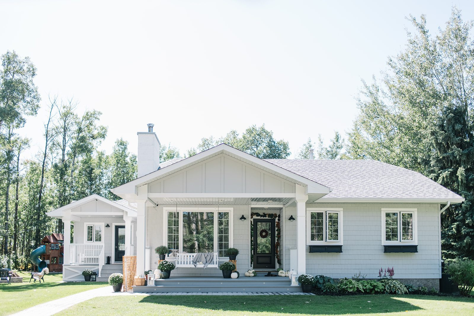 A modern farmhouse style exterior renovation created this single level home with grey siding, a black door and white windows