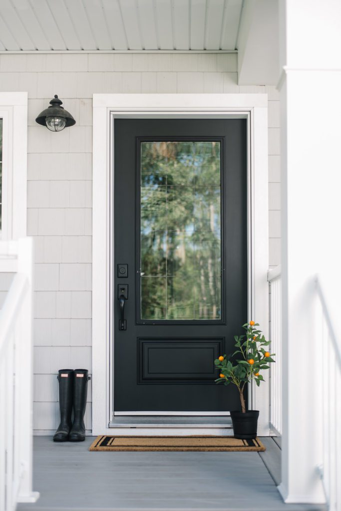 black front door with orange tree and boots sitting beside