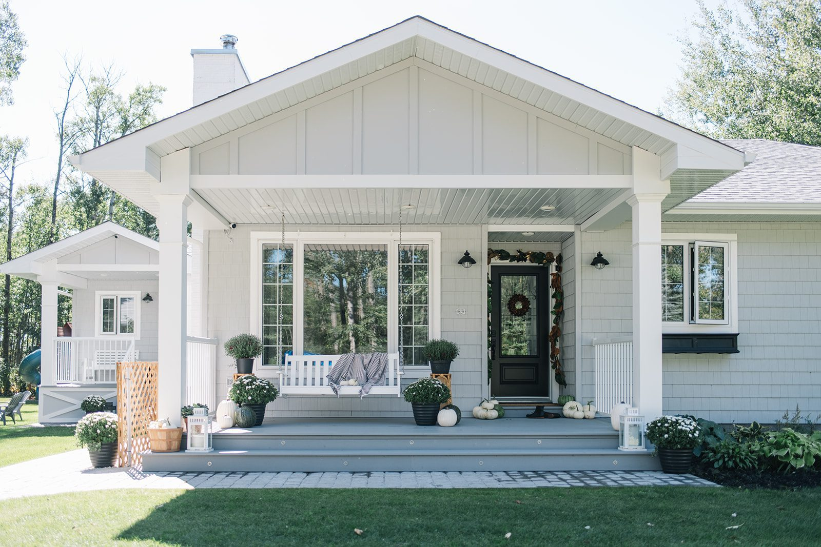 Modern country farmhouse with grey shingles and board and batten, black door and porch swing