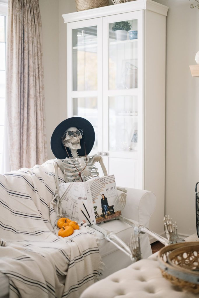 halloween skeleton sits on a couch reading a book