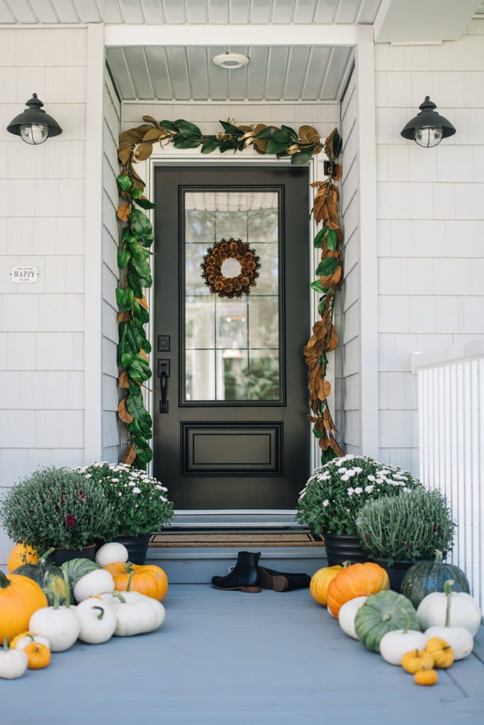 front door decorated for fall with magnolia garland and pinecone wreath
