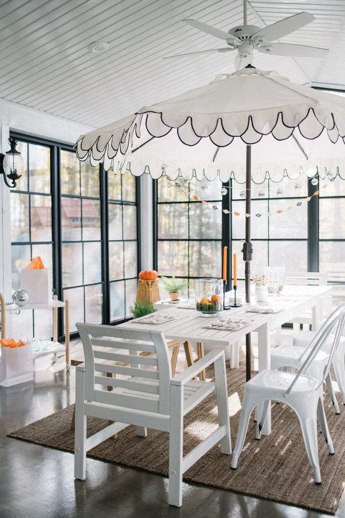sunroom set up for a Halloween party with an umbrella and orange candles