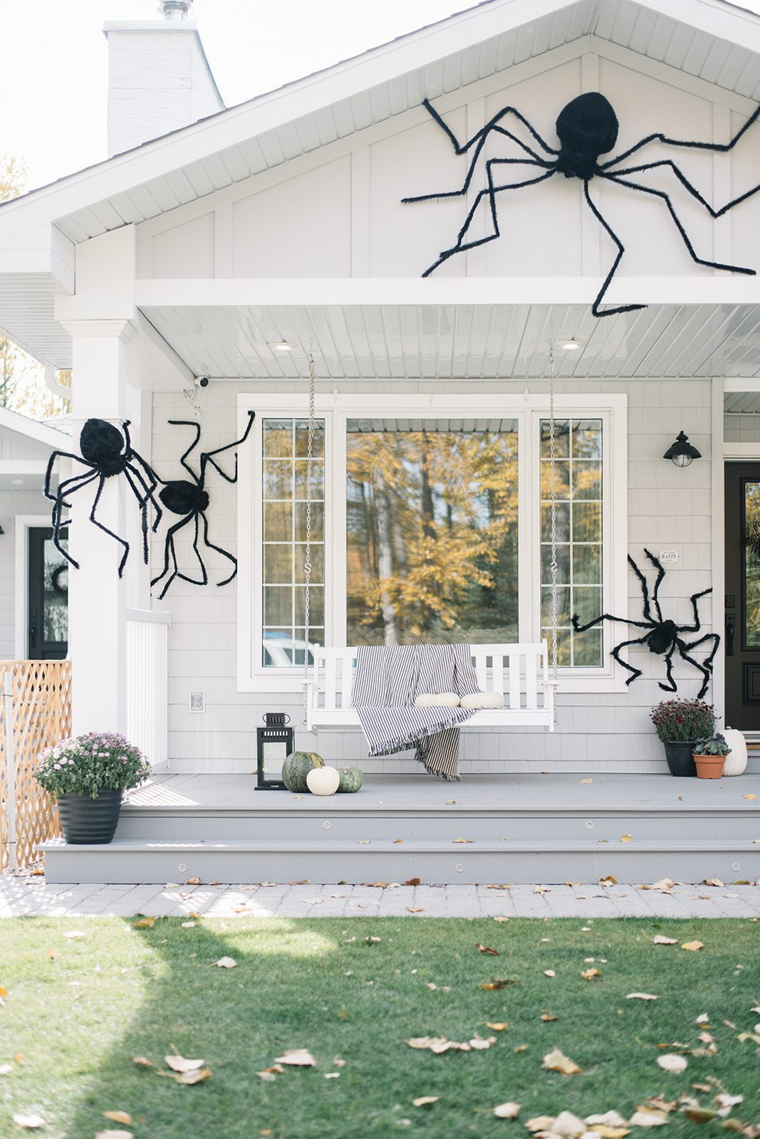 faux spiders attached to front porch pillars on house