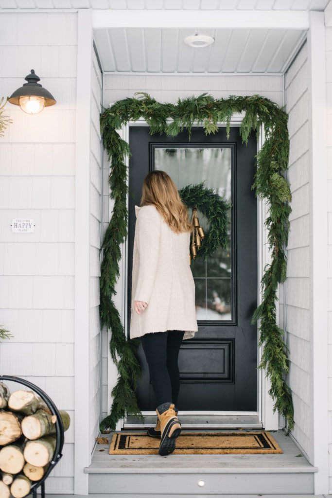 A woman walking into a front door decorated for Christmas