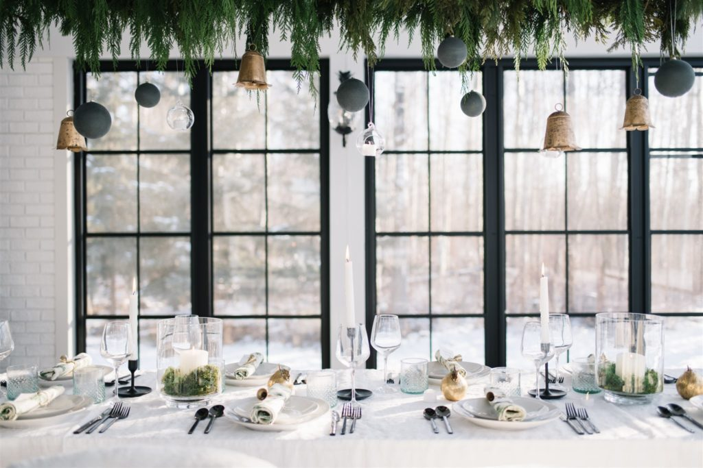 A modern country Christmas tablescape with hanging greenery and ornaments