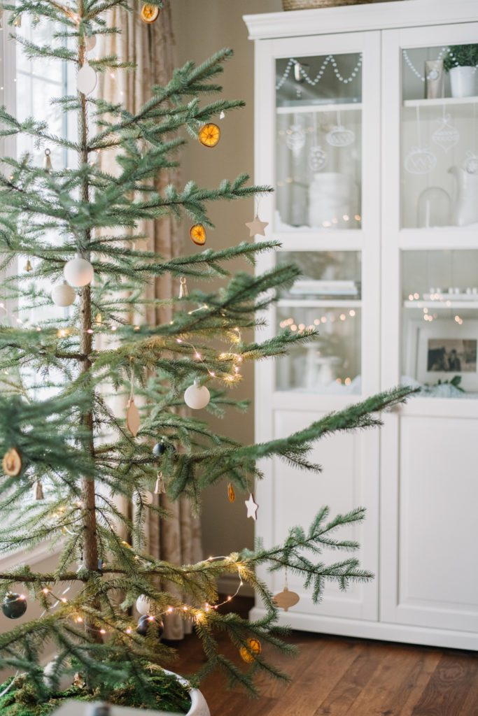 A sparse Christmas tree with white ornaments and dried oranges