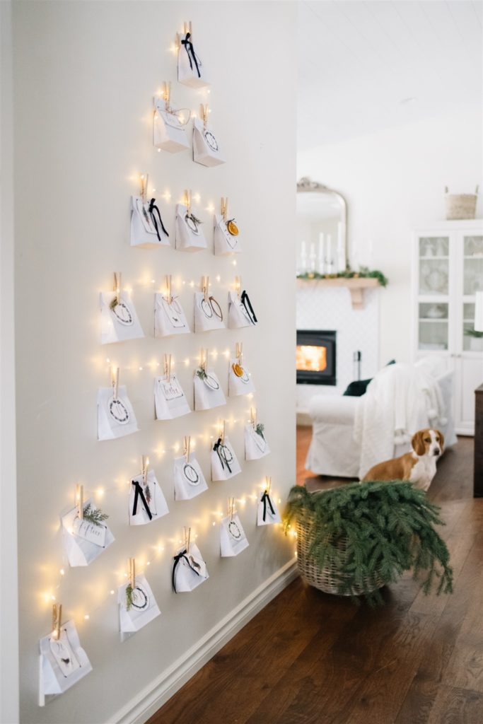 Christmas advent calendar on wall made from paper bags and twinkle lights