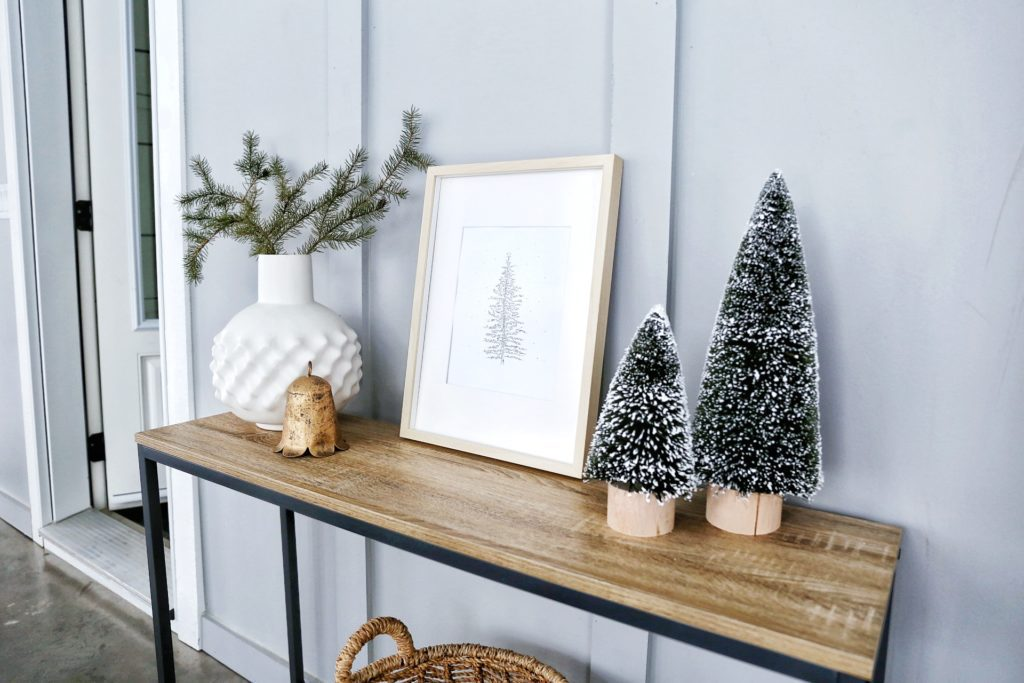 Framed print of a Christmas tree on a console table beside winter greens