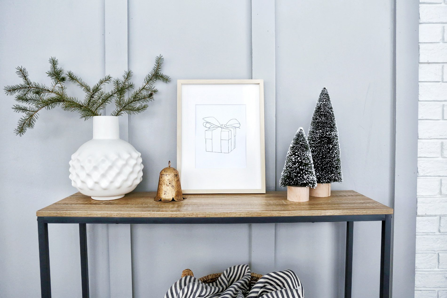 framed print of a present sits on a console table beside Christmas trees and a brass bell