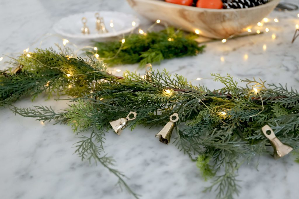 brass bell garland attached to faux greenery