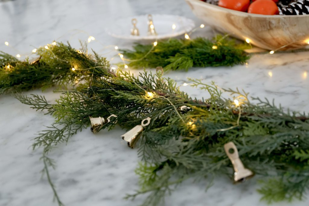 brass bells and twinkle lights with garland