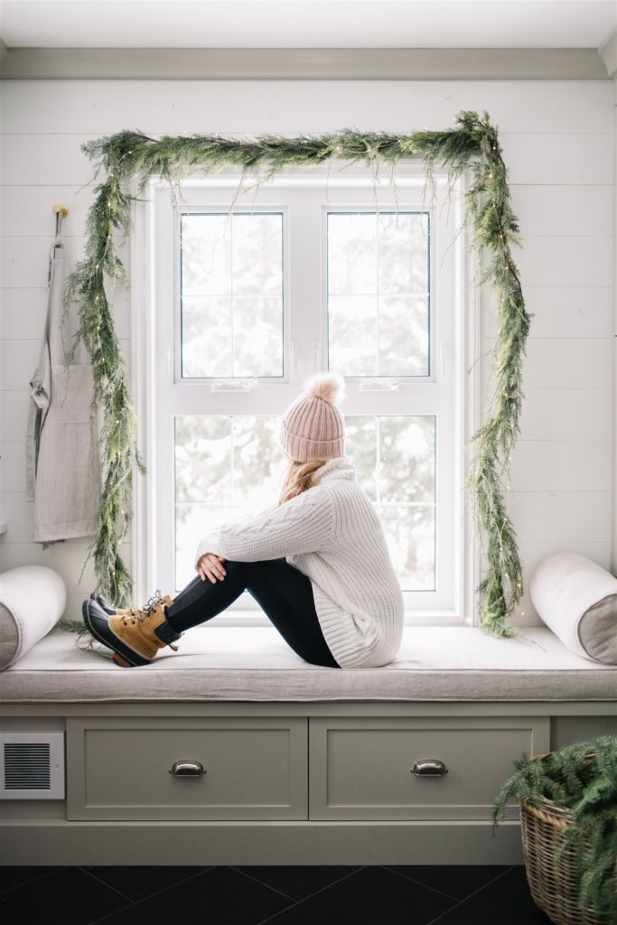 woman sitting in front of a window in winter boots and hat