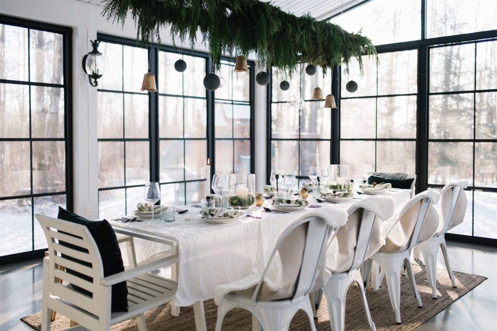 A sun room with a dining table set up for Christmas with greens and Christmas ornaments hanging above