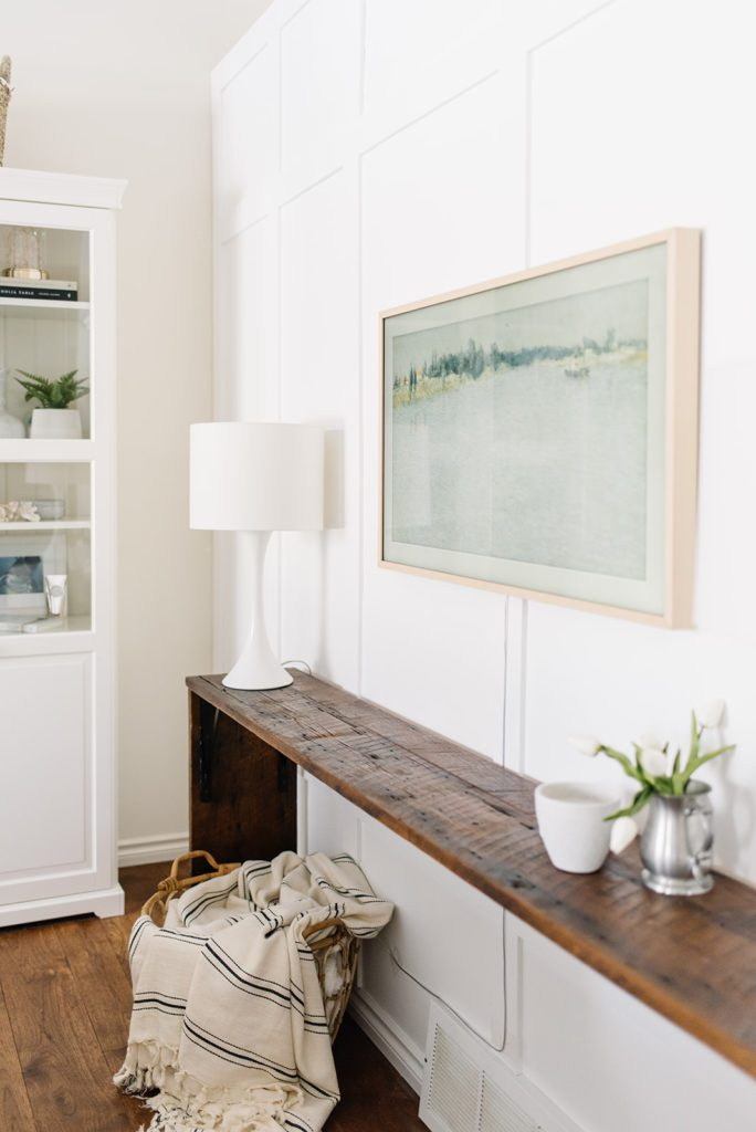 white oak framed TV above a wooden console table