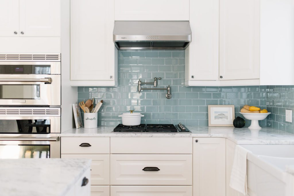 White kitchen with gas stovetop and stainless steel range hood