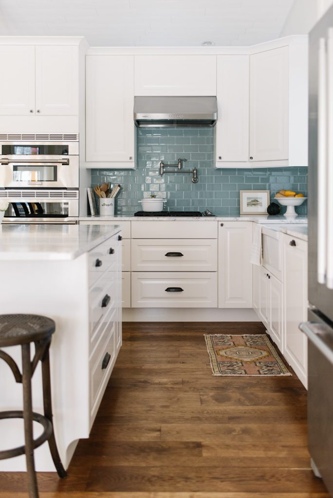 A kitchen with a wood floor, white cabinets and blue backsplash