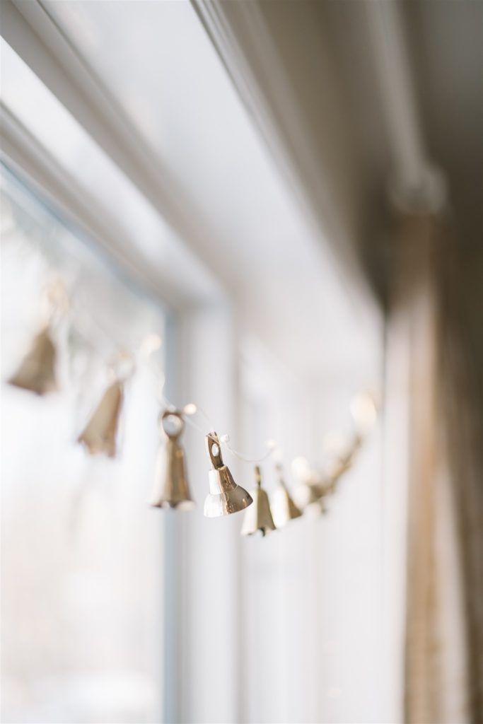 brass bell garlands hung in front of window