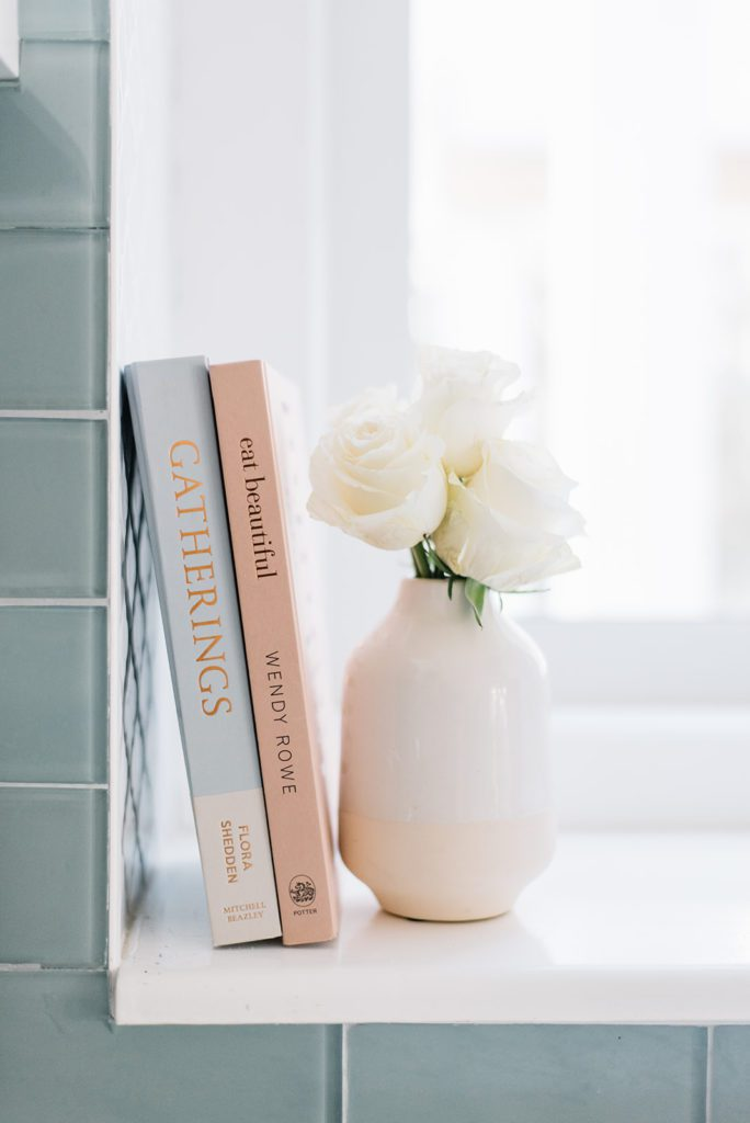 vase of roses and books on a ledge