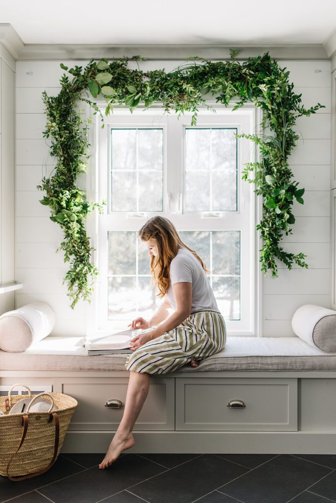 woman sits on bench reading book beneath fresh green garland over window